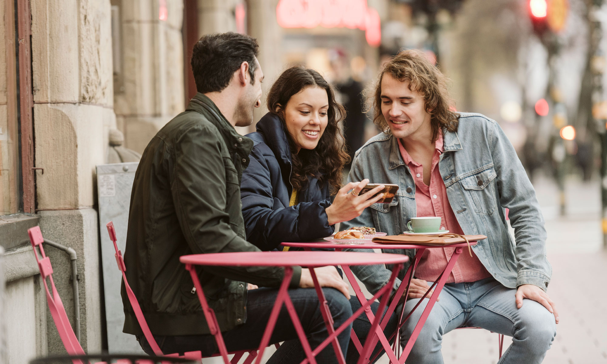 Three friends sitting outside a café.